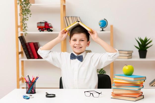 Speelse jongen spelen met boek Gratis Foto