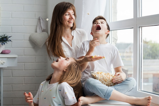 Speelse kinderen eten popcorn met hun moeder thuis Gratis Foto