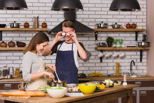Speelse man die ogen behandelt met eieren terwijl vrouw het koken Gratis Foto