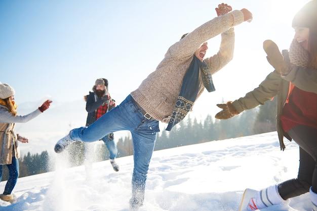 Speelse man met bemanning in de sneeuw Gratis Foto