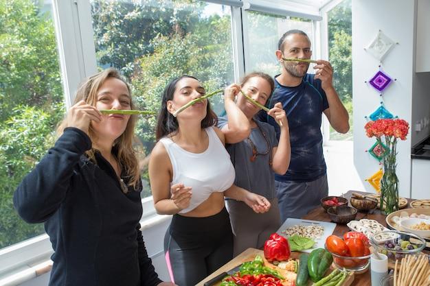 Speelse mensen maken valse snor van asperges Gratis Foto