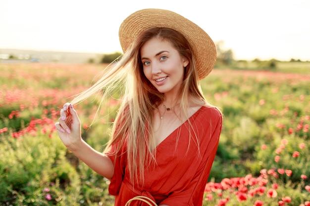 Speelse, onbezorgde blonde vrouw die graag poseren tijdens een wandeling buiten in een gelukkige stemming. met strooien hoed, oranje playsuit. papaver veld. Gratis Foto