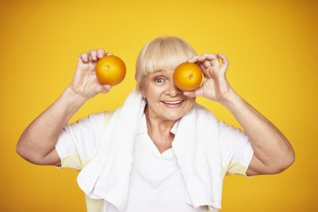 Speelse oude dame houdt sinaasappels vitamine c concept. Premium Foto