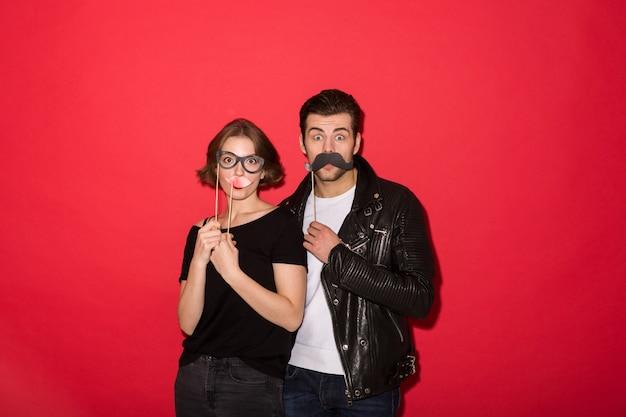Speelse punk paar poseren met nep snor, lippen en bril Gratis Foto