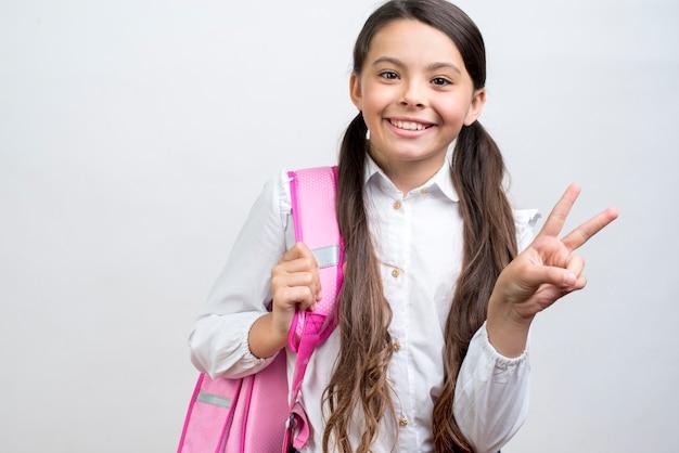 Speelse spaanse schoolmeisje dragende rugzak op schouder Gratis Foto