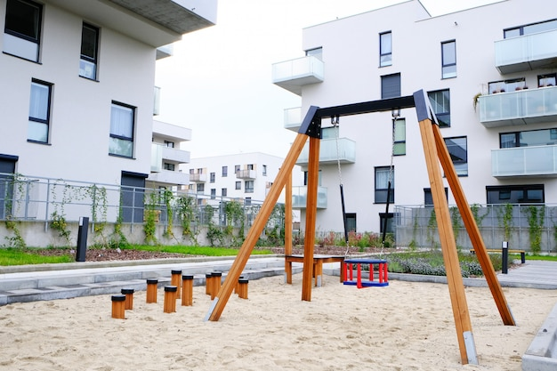Speeltuin met een schommel voor kinderen in de gezellige binnenplaats van de moderne woonwijk. Premium Foto