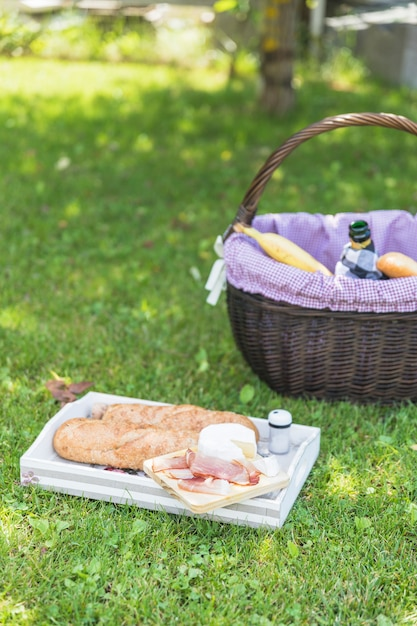 Spek; kaas en brood op dienblad met mand over groen gras Gratis Foto
