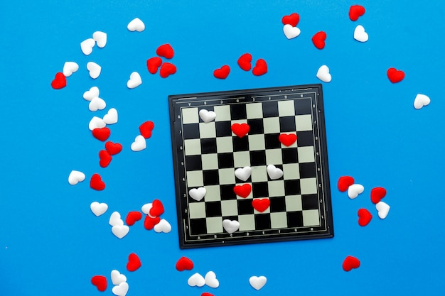 Spel van dammen met rode en witte harten op blauw Premium Foto