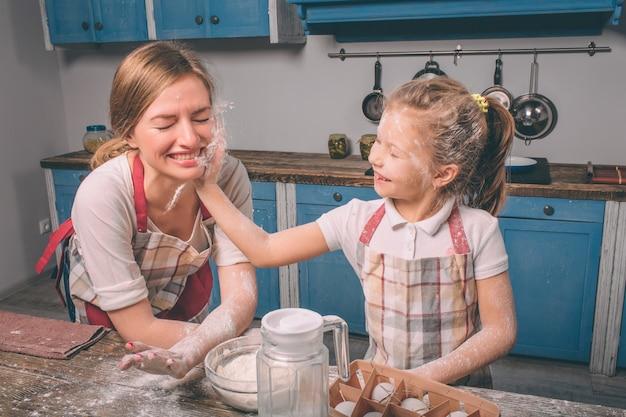Spelen met bloem. zelfgemaakt gebak koken. de gelukkige houdende van familie bereidt samen bakkerij voor. moeder en kind dochter meisje zijn koekjes koken en plezier in de keuken Premium Foto