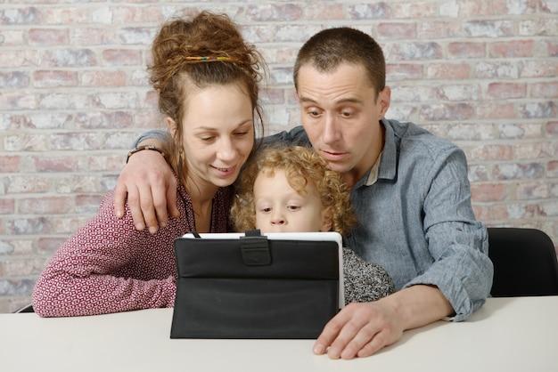 Spelen met een tabletcomputer en gelukkige familie Premium Foto