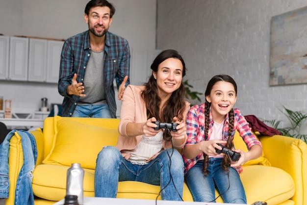 Spelen van videogames in woonkamer en gelukkige familie Gratis Foto