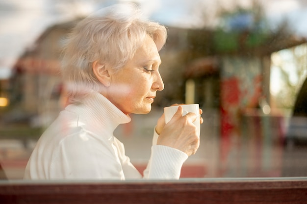 Spiegelend vrouwelijke senior koffie drinken Gratis Foto