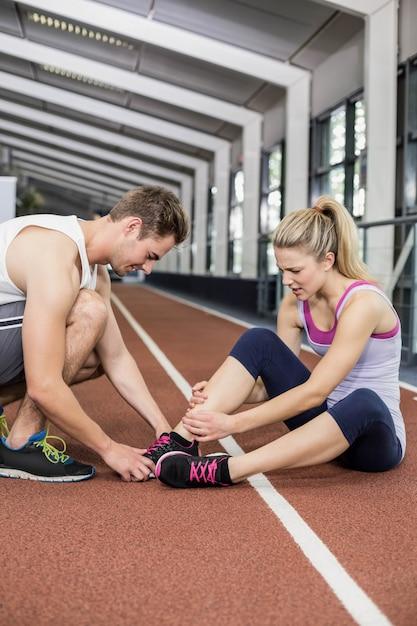 Spiervrouw die een enkelverwonding in crossfitgymnastiek hebben Premium Foto