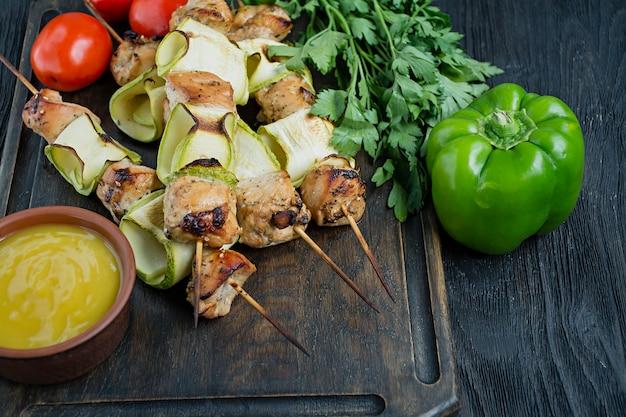 Spiesjes op een spies met courgette met saus en groenten op een snijplank Premium Foto