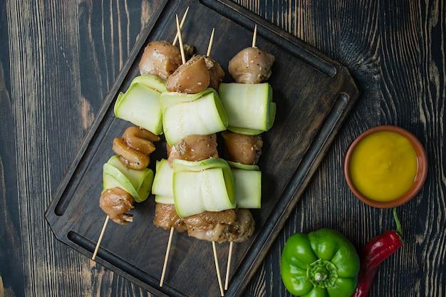 Spiesjes op een spies met courgette met saus, groenten en kruiden op een snijplank. donker houten. Premium Foto