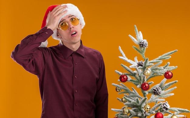 Spijt van jonge blonde man met kerstmuts en bril permanent in de buurt van versierde kerstboom opzoeken houden hand op hoofd geïsoleerd op een oranje achtergrond Gratis Foto