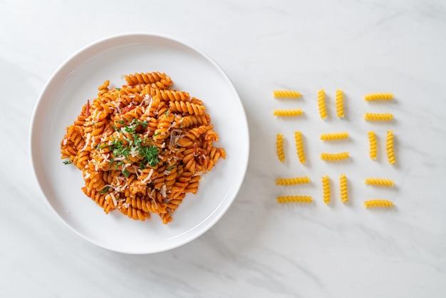Spiraal- of spiralipasta met tomatensaus en kaas. italiaanse eetstijl Premium Foto