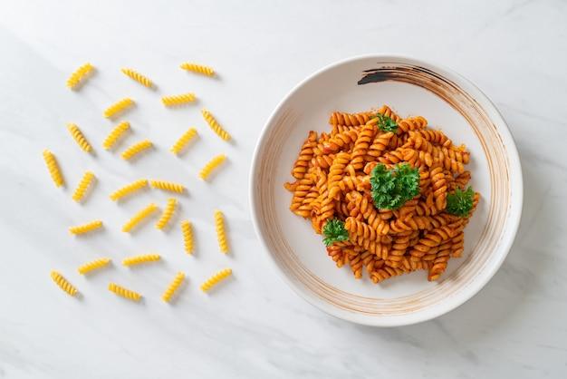 Spiraal- of spiralipasta met tomatensaus en peterselie. italiaanse eetstijl Premium Foto