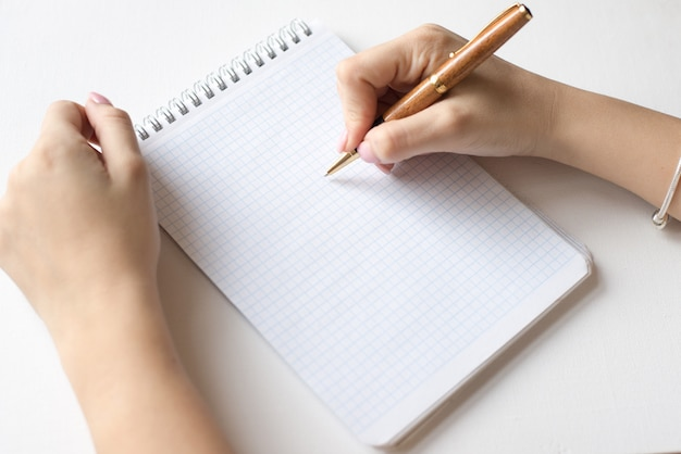 Spiraalvormig notitieboekje, witte pagina en pen, de pen van de vrouwengreep die op witte achtergrond wordt geïsoleerd Premium Foto