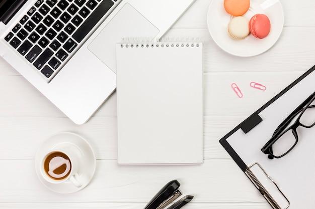 Spiraalvormige blocnote met laptop, makarons, koffiekop met klembord en oogglazen op wit bureau Gratis Foto