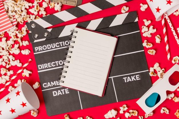Spiraalvormige blocnote op clapperboard met eenmalig glas; popcorns; rietje en 3d-bril op rode achtergrond Gratis Foto