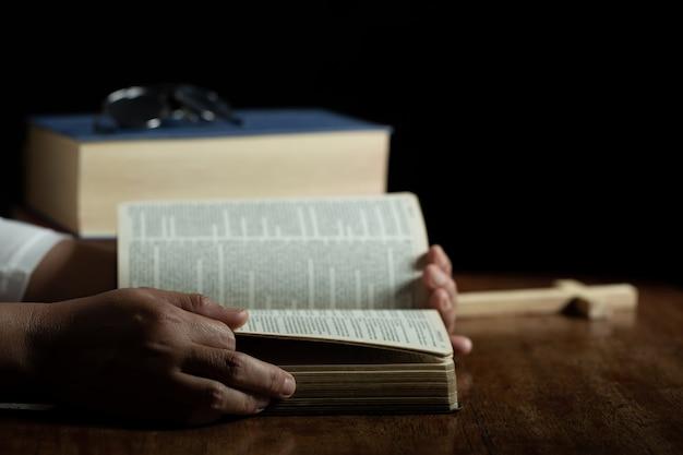 Spiritualiteit en religie, handen gevouwen in gebed op een heilige bijbel in de kerk Gratis Foto