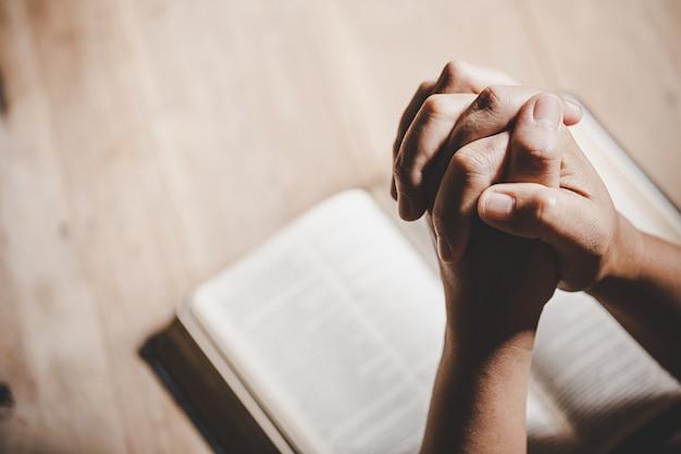 Spiritualiteit en religie, handen gevouwen in gebed over een heilige bijbel in kerk-concept voor geloof. Gratis Foto