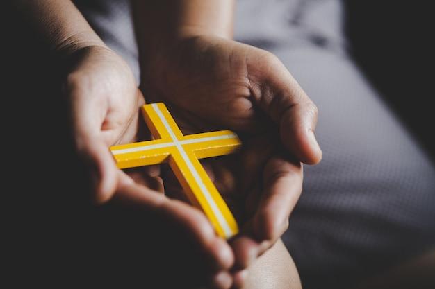 Spiritualiteit en religie, vrouwen in religieuze concepten handen bidden tot god terwijl ze het kruissymbool vasthouden. non ving het kruis in zijn hand. Gratis Foto