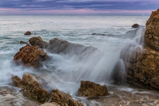 Splash en spray van golven tegen de rotsen. zonsondergang op de zee. Premium Foto