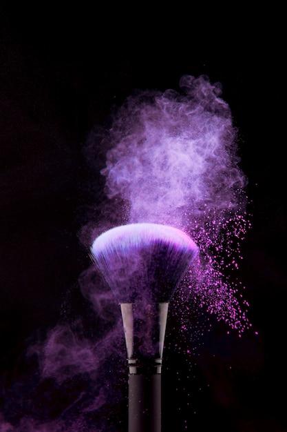 Splash van paars poeder op make-up borstel Gratis Foto