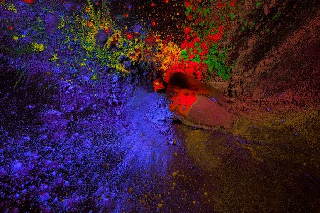 Splatter van holi kleurpoeder over zwart oppervlak Gratis Foto