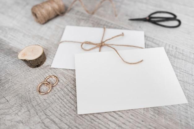 Spoel; miniatuur boomstronk; trouwringen; schaar en witte envelop op houten achtergrond Gratis Foto