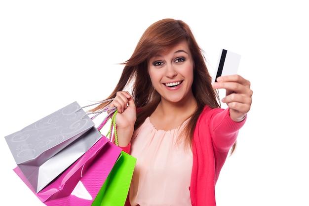 Spontane jonge vrouw creditcard tonen en boodschappentassen te houden Gratis Foto