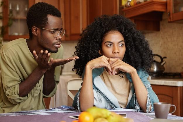 Spontane opname van ongelukkig jong afro-amerikaans echtpaar dat ruzie heeft thuis: schuldige, betreurenswaardige man met bril die zijn boze vrouw smeekt om vergeving, haar excuses aanbiedt omdat ze een grote fout heeft gemaakt Gratis Foto