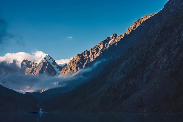 Spookachtig bos dichtbij bergmeer in vroege ochtend. de bergkreek van gletsjer stroomt in meer. mist op het wateroppervlak. lage wolk tussen rots. donker sfeervol mistig houtlandschap. rustige sfeer Premium Foto