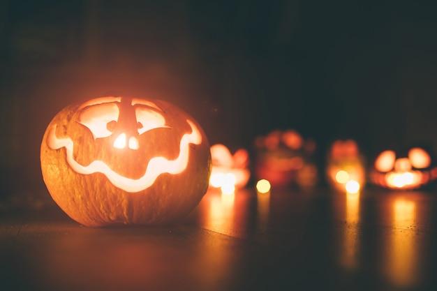 Spookpompoenen op halloween. ead jack op donkere achtergrond. vakantie indoor decoraties. Premium Foto