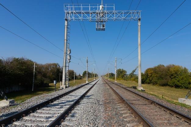 Spoorweg met elektrische draden die in de verte gaan. Premium Foto