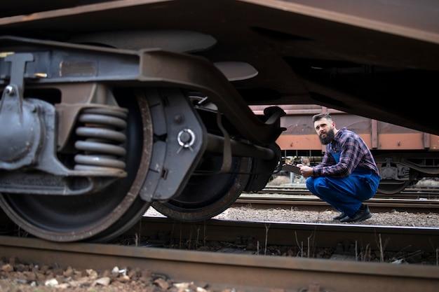 Spoorwegarbeider die wielen en remmen van de goederentrein inspecteert Gratis Foto