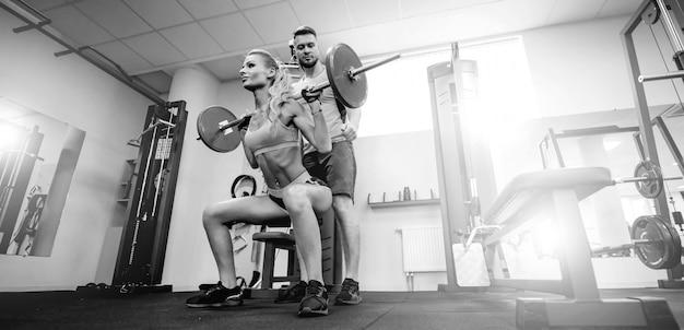 Sport, bodybuilding, levensstijl en mensenconcept - jonge man en vrouw met barbell buigende spieren en het maken van schouderpers hurkzit in gymnastiek. ondersteunde knielende positie, squat jogs. Premium Foto