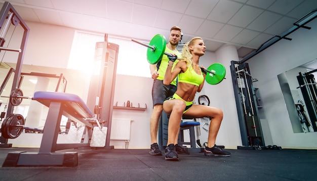 Sport, bodybuilding, levensstijl en mensenconcept - jonge man en vrouw met barbell buigende spieren en het maken van schouderpers hurkzit in gymnastiek. Premium Foto