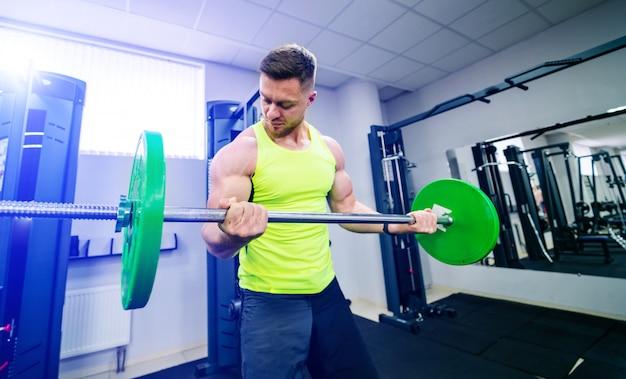 Sport, bodybuilding, levensstijl en mensenconcept - jonge mens met barbell buigende spieren en het maken van schouderpers hurken in gymnastiek. Premium Foto
