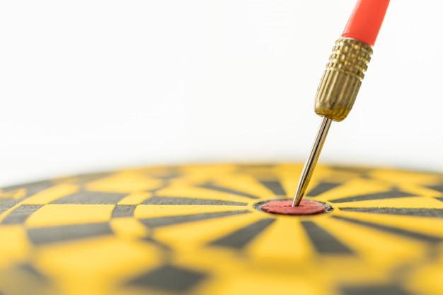 Sport, business, doel, planning en doel concept. sluit omhoog van rood pijltjeskant dat op centrum van zwart en geel dartboard wordt geraakt Premium Foto