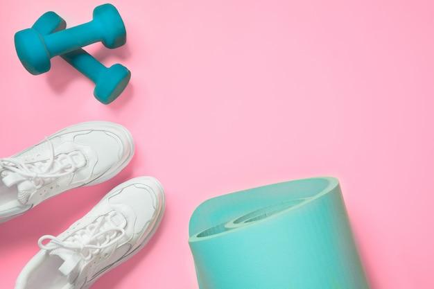 Sport- en fitnessschoenen, halter, yogamat op roze. Premium Foto