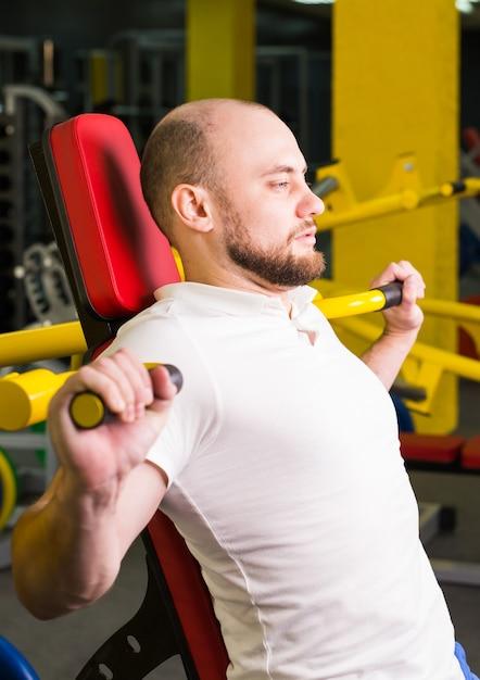 Sport, fitness, opleiding en mensen concept - gespierde man doet zware oefening oppompen van spieren in de sportschool. Premium Foto