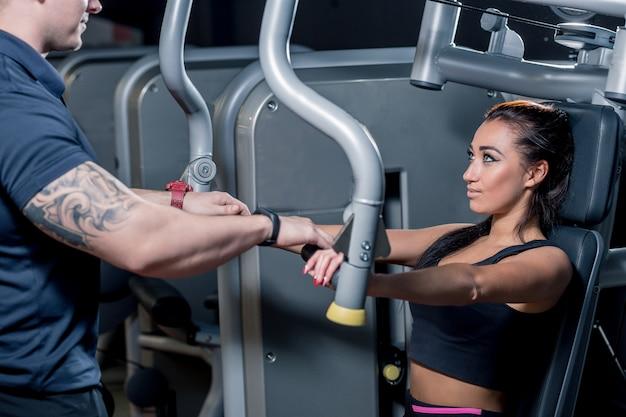 Sport, fitness, teamwork en mensen concept. jonge vrouw buigen spieren op gym machine en personal trainer met klembord Premium Foto