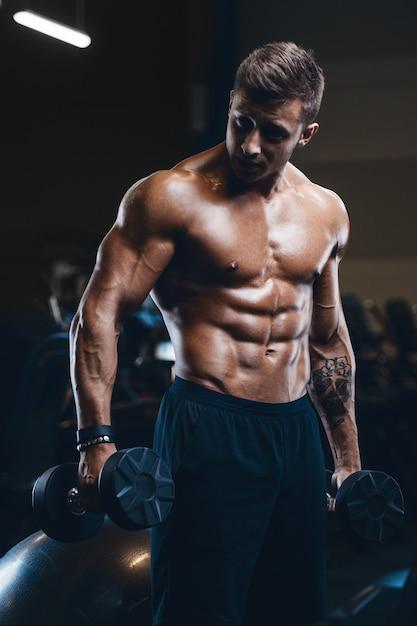 Sport gespierde fitness man uit te werken in de sportschool Premium Foto