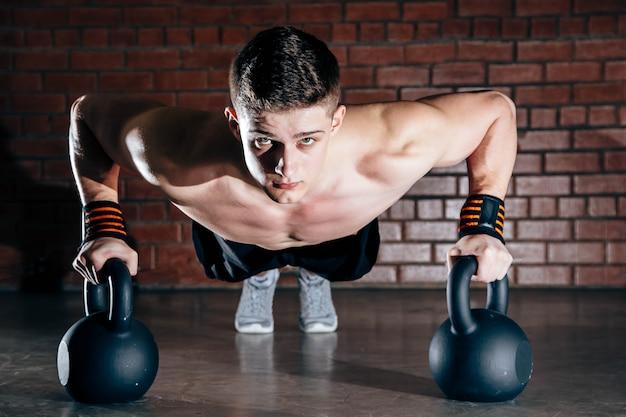 Sport. jonge atletische man doet push-ups. gespierde en sterke man oefenen. Premium Foto