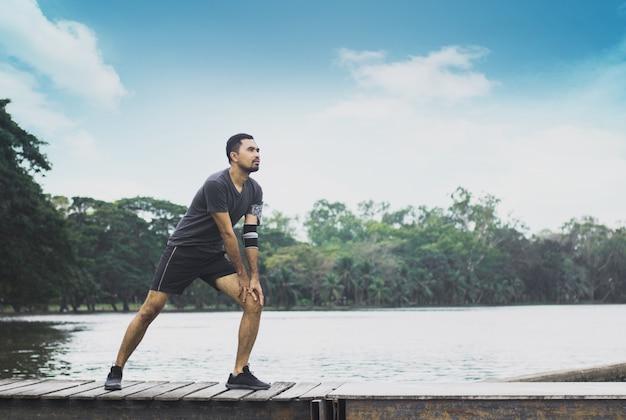 Sport man oefening en worm omhoog op de brug met de rivier Premium Foto