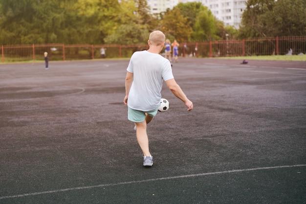 Sport man spelen met een voetbal in het stadion Premium Foto