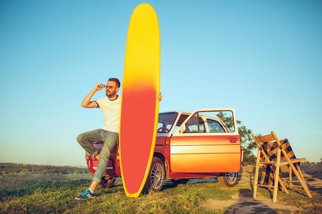 Sport, vakantie, reizen, zomerconcept. blanke man staande in de buurt van auto met surfplank op aard Gratis Foto